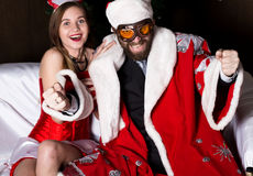 Brutal Santa Claus with female nurse sexy woman in carnival costume, driving on couch like on a car Stock Images