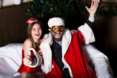 Brutal Santa Claus with female nurse sexy woman in carnival costume, driving on couch like on a car Royalty Free Stock Photo