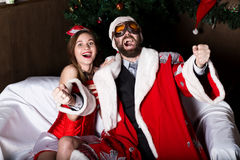 Brutal Santa Claus with female nurse woman in carnival costume, driving on couch like on a car stock image