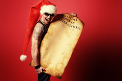 Brutal santa. Handsome brutal man in Christmas hat holding a list of good boys and girls. Over red background stock photography