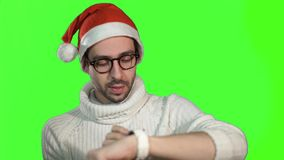 Brutal serious man in a cap of Santa Claus using smartwatch touch screen on a green background.  stock video