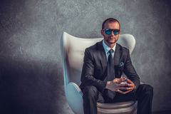 Brutal sexy businessmen in suit with tie and sunglasses sitting on chair Stock Photo
