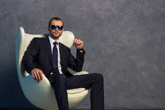 Brutal sexy businessmen in suit with tie and sunglasses sitting on chair. Stock Image