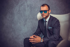 Brutal sexy businessmen in suit with tie and sunglasses sitting on chair Royalty Free Stock Photos