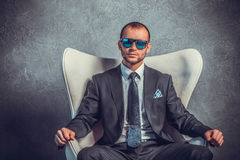 Brutal sexy businessmen in suit with tie and sunglasses sitting on chair. Stock Photography