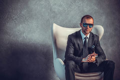 Brutal sexy businessmen in suit with tie and sunglasses sitting on chair Royalty Free Stock Images