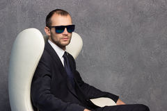 Brutal sexy businessmen in suit with tie and sunglasses sitting on chair Stock Photography