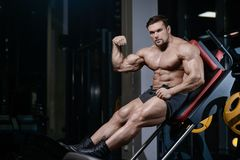 Brutal strong bodybuilder athletic men pumping up muscles with d. Brutal strong bodybuilder athletic fitness man pumping up abs muscles workout bodybuilding royalty free stock photo