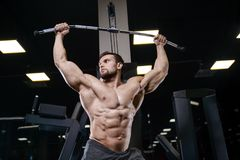 Brutal strong bodybuilder athletic men pumping up muscles with d. Brutal strong bodybuilder athletic fitness man pumping up abs muscles workout bodybuilding royalty free stock photos