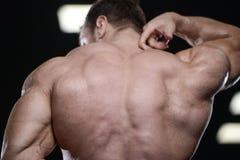 Brutal strong bodybuilder athletic men pumping up muscles with d. Brutal strong bodybuilder athletic fitness man pumping up abs muscles workout bodybuilding stock photos