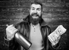 Brutal skäggig hipster för man att bära alkohol för drink för pengar för kassa för håll för läderomslag Svart kassa för olaglig v arkivbild