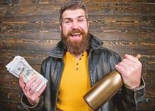 Brutal skäggig hipster för man att bära alkohol för drink för pengar för kassa för håll för läderomslag Svart kassa för olaglig v fotografering för bildbyråer