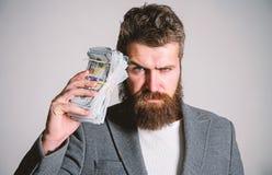 Brutal skäggig hipster för man att bära den formella dräkten och att rymma kassapengar Smart affär Olaglig vinst och svart kassa royaltyfria foton