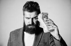 Brutal skäggig hipster för man att bära den formella dräkten och att rymma kassapengar Smart affär Olaglig vinst och svart kassa royaltyfri fotografi