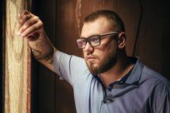 Brutal skäggig man med en tatuering på hans arm, stående av en man i dramatiskt ljus mot en brun trävägg, skäggig man med ta Royaltyfri Fotografi