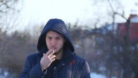 Brutal skäggig man som röker en utomhus- cigarett Arkivbild