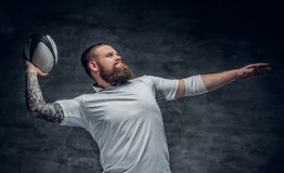 Brutal skäggig rugbyspelare i handling arkivfoton