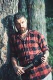 Brutal skogsarbetare som rymmer den lilla spaden och lutar på gammalt träd Hipster med det stilfulla skägget som irrar i vildmark fotografering för bildbyråer