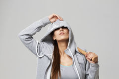 Brutal sportive girl in hood posing holding bit over white background. Royalty Free Stock Photos
