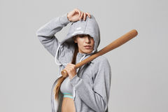 Brutal sportive girl in hood posing holding bit over white background. Copy space Royalty Free Stock Image
