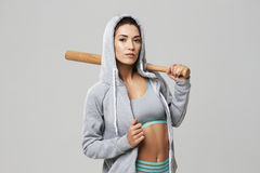 Brutal sportive girl in hood posing looking at camera holding bit over white background. Copy space Stock Photography