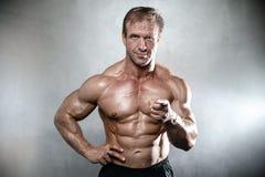 Brutal stark kroppsbyggaregamal man som poserar i studiogrå färgbackgrou Arkivfoto