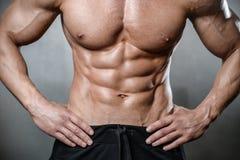 Brutal stark kroppsbyggareman som poserar i studio på grå backgroun Fotografering för Bildbyråer