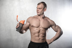 Brutal stark kroppsbyggareman som poserar i studio på grå backgroun Arkivfoto