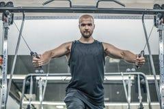 Brutal stilig Caucasian kroppsbyggare som utarbetar i idrottshallutbildningsbröstkorgen som upp pumpar withdumbbells för bröst- m royaltyfri bild