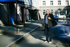Brutal street photographer with camera in hand strolling city streets. Full height portrait. In yard apartment buildings Royalty Free Stock Photography