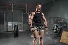 Brutal strong athletic men bodybuilder trains in the gym Stock Image