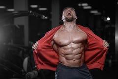 Brutal strong bodybuilder athletic men pumping up muscles with d. Brutal sexy strong bodybuilder athletic fitness man pumping up abs muscles workout bodybuilding Stock Images