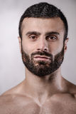Brutal strong bodybuilder man posing in studio on grey backgroun Royalty Free Stock Photography