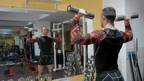 Brutal strong bodybuilder pumping up muscles, doing exercises in gym.  stock footage