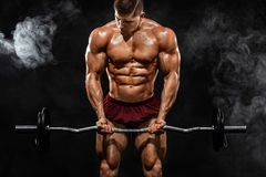 Brutal strong muscular bodybuilder athletic man pumping up muscles with barbell on black background. Workout royalty free stock photos