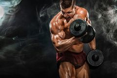 Brutal strong muscular bodybuilder athletic man pumping up muscles with dumbbell on black background. Workout stock photography