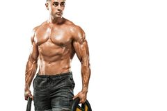 Brutal strong muscular bodybuilder athletic man pumping up muscles with dumbbell on white background. Workout stock image