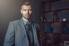 Brutal stylish man in suit with fashionable hairdo in luxurious interior of apartment. Handsome businessman in rich house. Brutal stylish man in suit with stock images