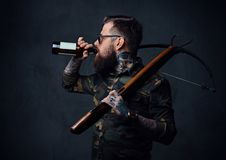A man holds the craft beer bottle and a crossbow. A brutal tattooed, bearded male dressed in a military jacket holds the craft beer bottle and a crossbow Royalty Free Stock Images