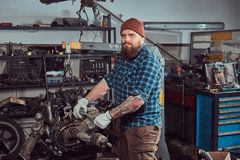 A brutal tattooed bearded mechanic specialist repairs the car engine which is raised on the hydraulic lift in the garage stock photography