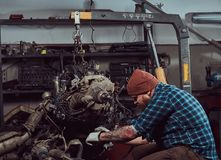 A brutal tattooed bearded mechanic specialist repairs the car engine which is raised on the hydraulic lift in the garage royalty free stock photography