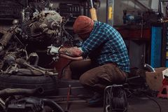 A brutal tattooed bearded mechanic specialist repairs the car engine which is raised on the hydraulic lift in the garage royalty free stock image
