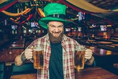 Brutal ung skäggig man i grön hattställning bara i bar Han rymmer två rånar av öl och blick på kamera Grabbhjärnskrynklare Honom royaltyfri bild