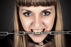 Brutal woman with a chain in teeth. Portrait of a brutal woman with a chain in teeth Stock Photos
