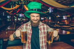 Brutal young bearded man in green hat stand alone in pub. He hold two mugs of beer and look on camera. Guy shrink. He royalty free stock image