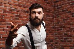 Brutal young handsome man smoking cigar over brick background. Stock Images
