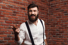 Brutal young handsome man smoking cigar over brick background. Stock Photography