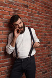 Brutal young handsome man smoking cigar over brick background. Stock Image