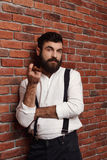 Brutal young handsome man smoking cigar over brick background. Stock Photo