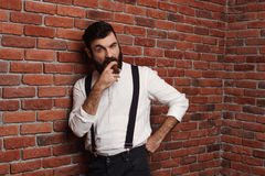 Brutal young handsome man smoking cigar over brick background. Royalty Free Stock Photography